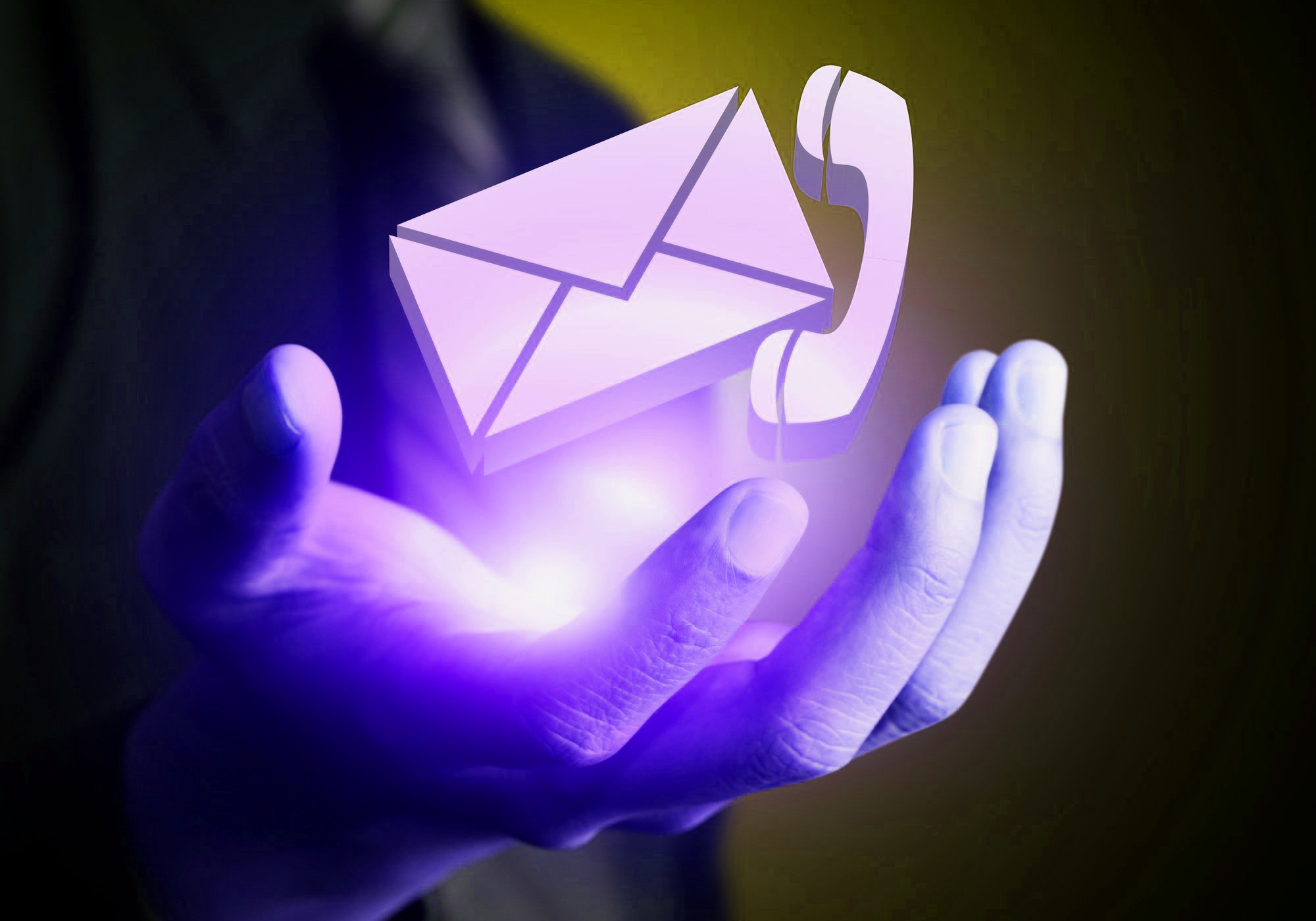 Glowing phone and email icons in a man's hand